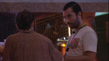 Gilberto está conversando com Fiuk (de costas) com semblante sério na festa do BBB21