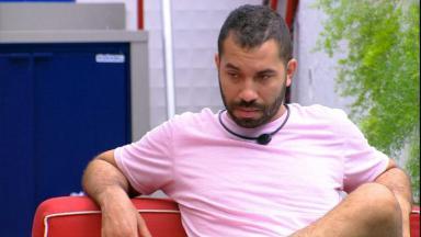 Na área externa, Gilberto está sentado pensativo