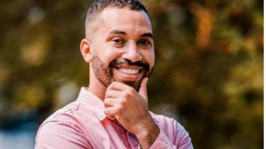 Gilberto posando para foto sorrindo com a mão no rosto