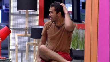 Gilberto sentando em banco na sala do BBB21 conversando com uma mão no cabelo