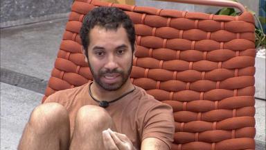 Gilberto está sentado na área externa do BBB21