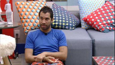 Gilberto está sentado no chão da sala do BBB21