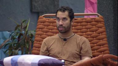 Gilberto está sentado sozinho na área externa do BBB21