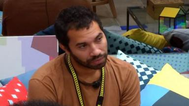 Gilberto está sentado na sala do BBB21