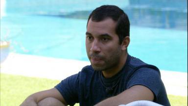 Gilberto está sentado no gramado do BBB21