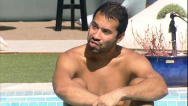 Gilberto está sentado na borda da piscina do BBB21