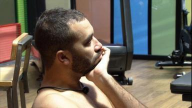 Na academia, Gilberto está com a mão no queixo analisando painel tático do BBB21