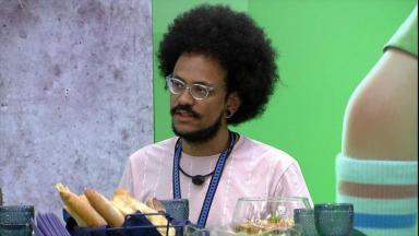 João Luiz conversando sentado em frente à mesa posta do almoço do anjo