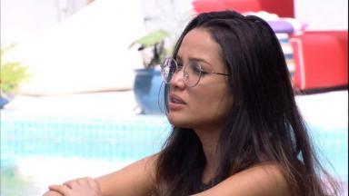 Juliette conversando na área externa do BBB21 com a piscina ao fundo