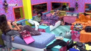Juliette está em pé no quarto colorido maquiando Thaís que está deitada na cama do BBB21