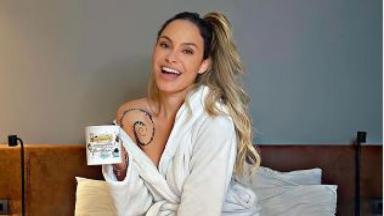 Sarah posa com uma caneca na mão sentada na cama após BBB21