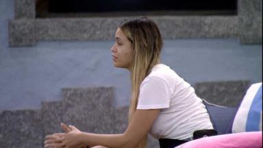 Sarah sentada na área externa do BBB21