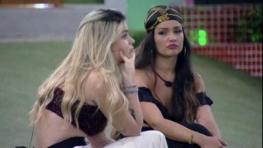 Viih Tube está com a mão no queixo e Juliette está olhando para a sister na área externa do BBB21