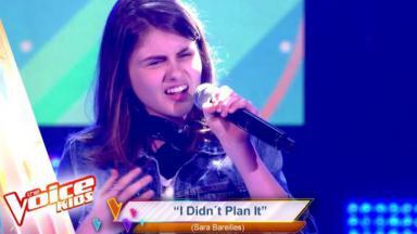 Bel com o microfone na mão cantando no The Voice Kids