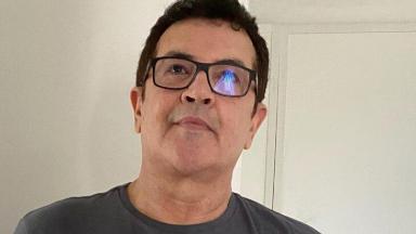 Beto Barbosa de óculos, tirando foto em frente ao espelho