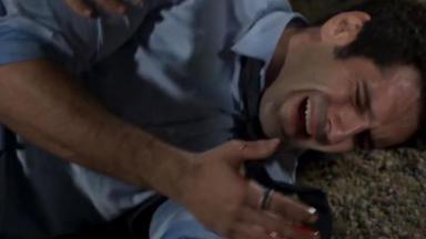 Beto deitado no chão, chorando de dor e com sangue nas mãos
