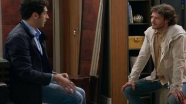 Beto sentado de frente para Henrique tenta se explicar