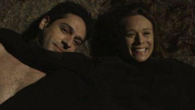 Beto e Tancinha deitados no chão, cobertos com o paletó do publicitário ele com cara de apaixonado e ela rindo.