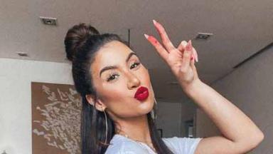 Bianca Andrade fazendo sinal de V com a mão esquerda