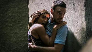 Bibi muito assustada abraça Rubinho que tenta protegê-la dos tiros