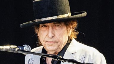 Bob Dylan de chapéu diante de microfone