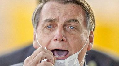 Bolsonaro gritando com a máscara no queixo