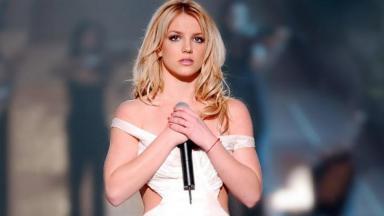 Britney Spears com a expressão preocupada, segurando o microfone com as duas mãos no peito