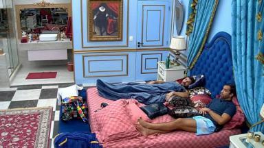 Caio está deitado ao lado de Gilberto na cama do quarto de líder do BBB21