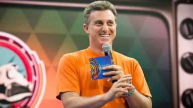 Luciano Huck de camiseta laranja segurando microfone e ficha do Caldeirão do Huck