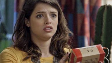 Camila segura o pacote com o olhos arregalados de susto