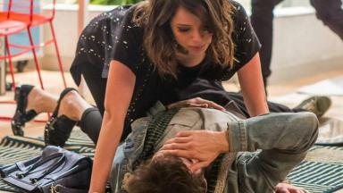 Giovanni caído no chão com a mão no rosto e Camila debruçada sobre ele
