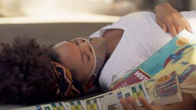 Camila desacordada, caída no chão com livros espalhados