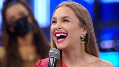 Carla Diaz rindo e segurando o microfone no palco do Domingão