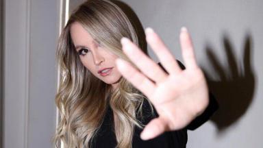Carla Diaz com a mão na frente da câmera, posada para foto