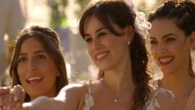 Natália estende a mão para Juliano enquanto Mila e Carol observam sorrindo