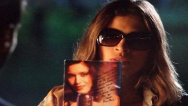 De óculos escuros, Ester segura DVD com dedicatória de Cristal na direção de Cassiano