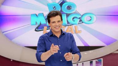 """Celso Portiolli à frente do logo do """"Domingo Legal"""", no palco da atração"""