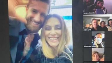 Cleo ao lado do marido em videoconferência com a família