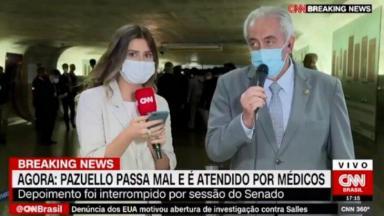 Repórter da CNN perdida ao vivo, com microfone e celular nas mãos, enquanto o senador Otto Alencar olha desviado