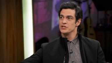 Mateus Solano sentado enquanto concedia entrevista com um microfone em sua frente