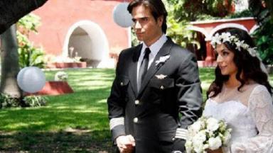 Cena de Coração Indomável com Maricruz vestida de noiva de mãos dadas com Otávio, que está como piloto