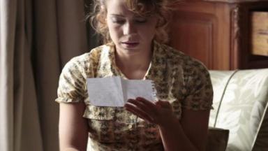 Cristina sentada na cama lendo carta