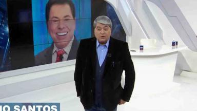 Datena no Brasil Urgente, com Silvio Santos ao fundo no telão