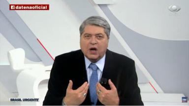 Irritado durante programa, Datena aparece de boca aberta com as mãos perto do peito