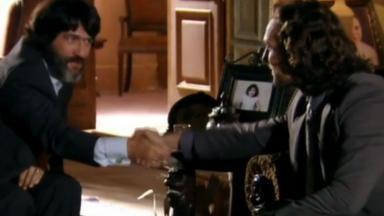 Sentados de frente um para o outro, Dom Rafael e Alberto se encaram enquanto selam acordo com um aperto de mãos