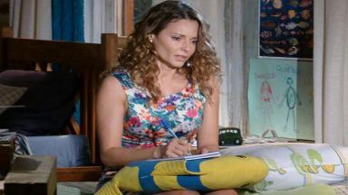 Doralice chora sentada a cama enquanto escreve um bilhete de despedida