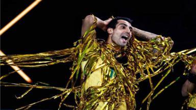 O atleta da seleção masculina de voleibol, Douglas Souza com a camisa do Brasil e com fitas douradas e de boca aberta