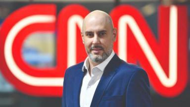 Douglas Tavolaro ao lado de uma TV com o logo CNN