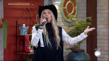 Adriane Galisteu de chapéu com o microfone na mão direita e abrindo o braço esquerdo