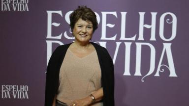 Elizabeth Jhin, autora que não tem mais contrato com a Globo, a frente de um cartaz com o logo de Espelho da Vida
